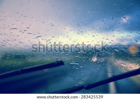 Dangerous blurry driving car in the rainy and slippery road. Rain through windshield of moving car on highway. Car windshield wipers on in the rainy weather. - stock photo