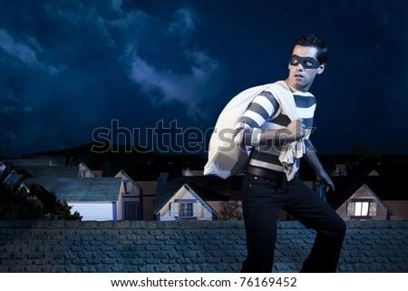 dangerous burglar about to enter house - stock photo