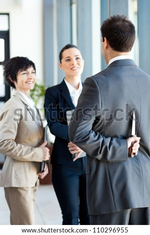 dangerous businessman hiding knife behind his back while handshaking with businesswoman - stock photo