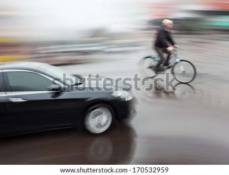 Dangerous city traffic situation with a cyclist and cars in motion blur - stock photo