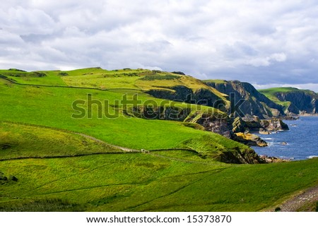 dangerous cliffs  covered with a green pasture on cloudy day - stock photo