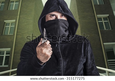 Dangerous criminal holding a knife. Cross processed image for dramatic look. - stock photo
