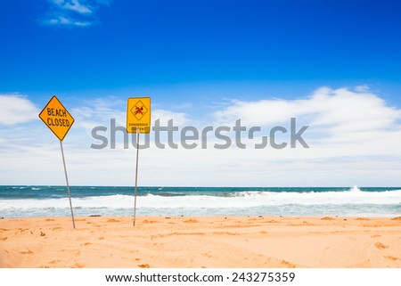 dangerous current and beach closed sign on the beach - stock photo