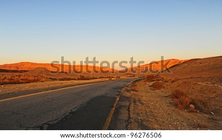 Dangerous Curves Road Sign at the Abandoned Road. Sunset - stock photo