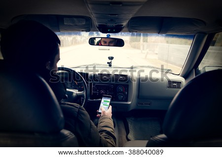 Dangerous driving while writing SMS text message - stock photo