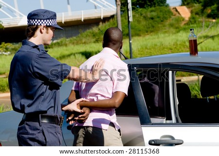 dangerous drunk driver been arrested by policeman, a bottle of wine still on the car - stock photo