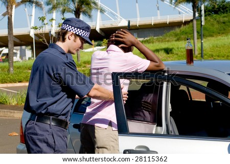 dangerous drunk driver been searched by policeman, a bottle of wine still on the car - stock photo