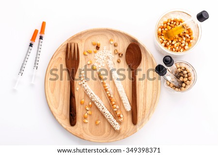 Dangerous food from  laboratory agricultural grains and corn with wooden fork and spoon isolated on white background GMO food concept. - stock photo