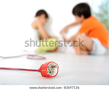 Dangerous game, children experimenting with electricity, plug in - stock photo
