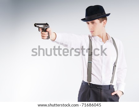 Dangerous gangster in hat holds a pistol and aims - stock photo