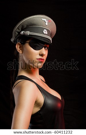 dangerous gorgeous girl with a german officer hat and a patch over a dark background - stock photo