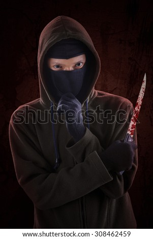 Dangerous killer standing in the dark and holding a bloody knife