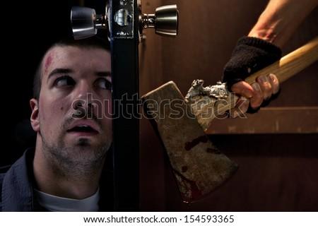 Dangerous killer wirh axe on the other side of the door - stock photo