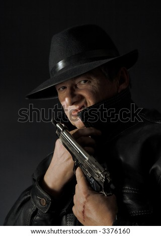 Dangerous looking mafia type with revolver and leather jacket - stock photo