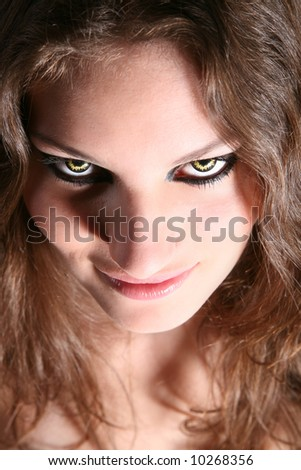 Dangerous looking woman with fierce yellow eyes - stock photo