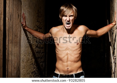 Dangerous male vampire standing between walls in an old Viennese cellar - stock photo
