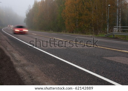 Dangerous mist on country road in forest with fast moving cars