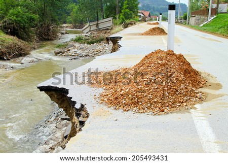 Dangerous pile on part of road caused by erosion after flooding - stock photo