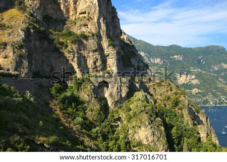 Dangerous road along the side of the cliffs of the Amalfi coast in Italy - stock photo