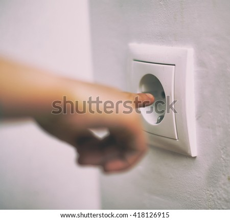Dangerous situation at home. Child playing with electrical socket. - stock photo