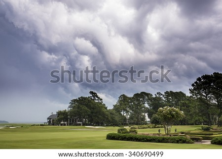 Dangerous storm moving over golf course - stock photo