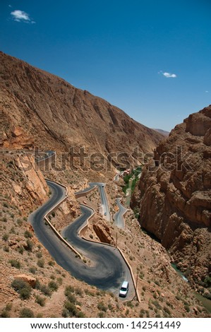 Dangerous turn on the highway pass in Moroccan High Atlas Mountain on hot summer day. Winding road in the river valley.