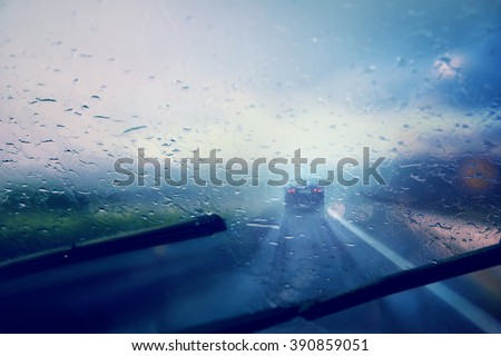 Dangerous vehicle driving in the heavy rainy and slippery road. Raindrops on windshield of moving car on highway. Abstract blurred bad weather vehicle driving. - stock photo