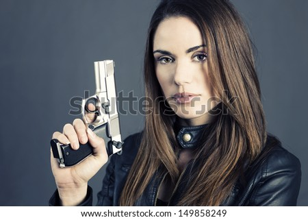 Dangerous woman holding up her gun - stock photo