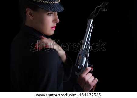 Dangerous woman in black with silver smoking handgun and stylish hat