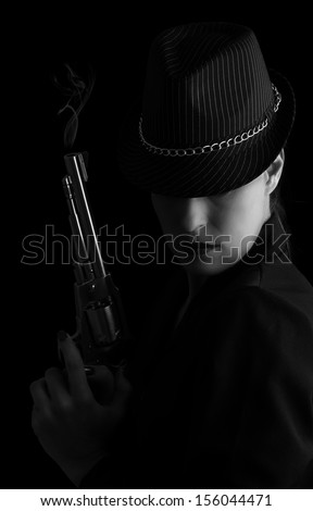 Dangerous woman in black with silver smoking handgun and stylish hat artistic conversion - stock photo