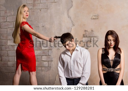 Dangerous woman pointing her gun to a man because of infidelity - stock photo