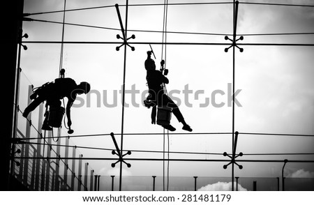 Dangerous working of a man on high Tower in the city with skycraper windows cleaner on black and white color