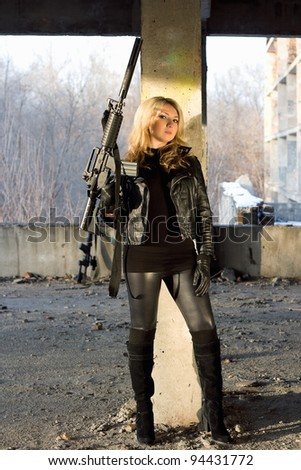 Dangerous young woman with rifle leaned against  the wall - stock photo