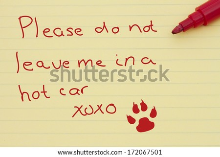 Dangers of leaving a dog in parked cars, Yellow Lined Paper with a note from your pet, paw print and a marker - stock photo