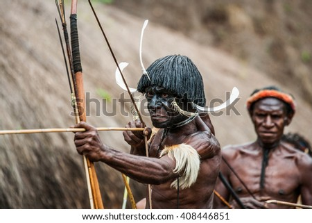DANI VILLAGE, WAMENA, IRIAN JAYA, NEW GUINEA, INDONESIA 15 MAY 2012: Men Dani tribe shoot an arrow. May 15, 2012 The Baliem Valley, Indonesian, New Guinea - stock photo