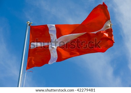 danish flag on a pole against blue sky - stock photo