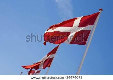 Danish flags waving against the blue summer sky. Space for text. - stock photo