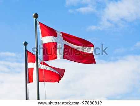 danish flags with blue sky on background - stock photo
