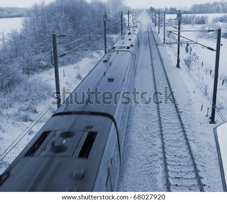 Danish intercity train on a cold December day in the countryside. - stock photo