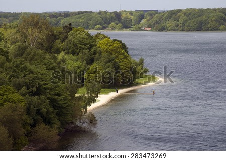 Danish landscape. View from The Littlebelt Bridge. Divers going on the beach. - stock photo