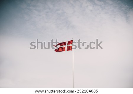 Danish national flag waving on the blue sky background - stock photo