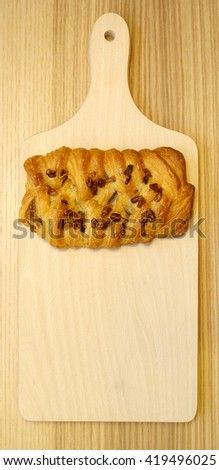 Danish pastry with nuts and honey. Baked. Space for text. Wooden background.