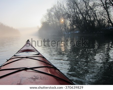 DANUBE RIVER, UKRAINE - JANUARY 30, 2016: Winter kayaking in foggy winter Danube river.