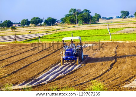 DAOLA, INDIA - OCT 25: A ractor plows the field on October 25, 2013 in Daola, India. Agriculture contributes 21 percent of India's GDP, but the rural areas are still home to some 72 percent of the Indians people. - stock photo