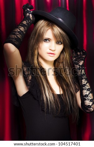 Dapper young showgirl in theatre costume doffing her bowler hat with a gloved hand in a sign of greeting and acknowledgement of the audience at a live perormance - stock photo
