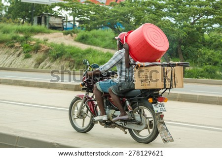 Dar Es Salaam: April 22: A man hires a bodaboda (Motorcycle) taxi to carry items he has purchased at the local market on April 22, 2015 in Dar Es Salaam, Tanzania - stock photo
