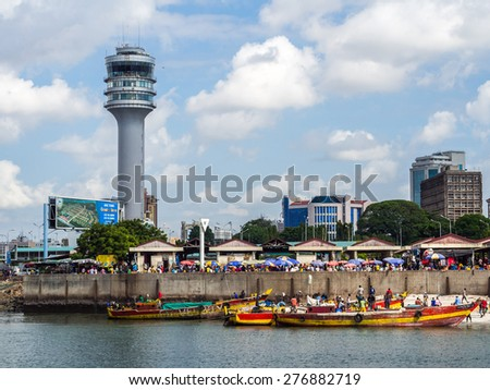 DAR ES SALAAM, TANZANIA - MAY 01, 2015: Horizontal photo of the waterfront of Dar es Salaam, Tanzania in East Africa, with maritime control tower and the fish market. Local people on boats in front.  - stock photo