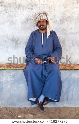 DARAW, EGYPT - FEBRUARY 6, 2016: Local camel salesman holding glass and cigarette. - stock photo