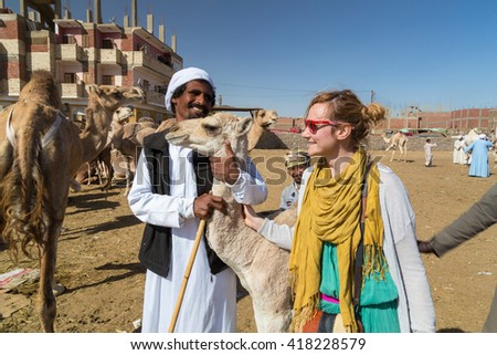 DARAW, EGYPT - FEBRUARY 6, 2016: Tourist and local camel salesmen at camel market. - stock photo