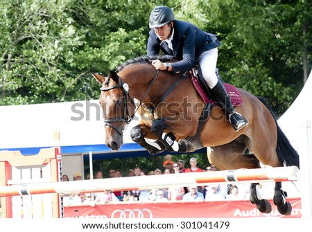 DARGUZIAI,LITHUANIA-JULY 13: Rider with horse above a fence in the Lithuanian Open Show Jumping Championship 2013 VMG Cup at the Horsemarket horse riding center  on 13 July,2013 in Darguziai,Lithuania